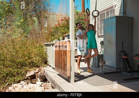 Mid adult man lifting daughter sur bagues d'exercice on patio Banque D'Images