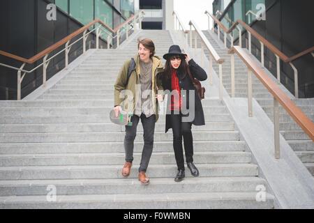 Jeune couple d'caucasian woman and man, avec la raie et moustache, descendant les escaliers hugging et souriant Banque D'Images