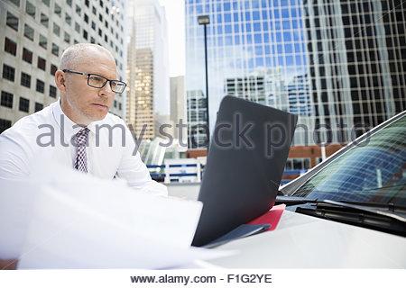 Businessman using laptop on car en ville Banque D'Images