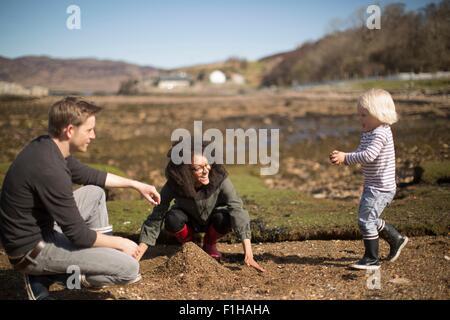 Mère et père jouant avec fils, ce tas de terre Banque D'Images