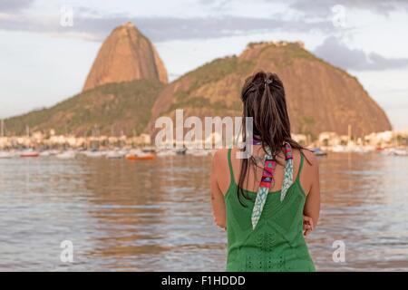 Mid adult woman looking out vers le mont Sugarloaf, baie de Botafogo, Rio de Janeiro, Brésil Banque D'Images