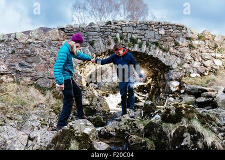 Jeune couple hiking, Ashness Bridge, Keswick, Lake District, Cumbria, Royaume-Uni Banque D'Images
