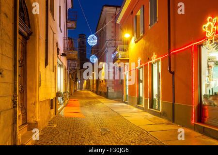 Rue pavées étroites entre les maisons illuminée et décorée pour Noël et Nouvel An vacances en ville d'Alba. Banque D'Images