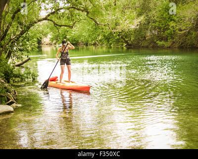 Femme stand up paddle boarding sur Barton Creek, Austin, Texas Banque D'Images