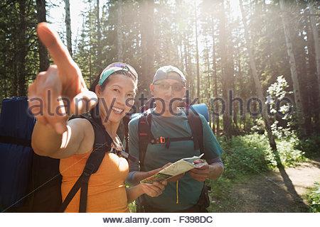 Backpackers avec carte indiquant à sunny woods Banque D'Images