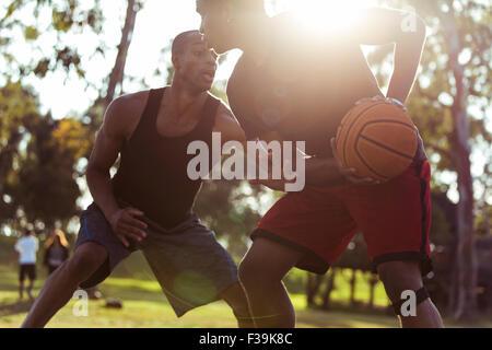 Deux jeunes hommes jouant au basket-ball dans le parc au coucher du soleil Banque D'Images