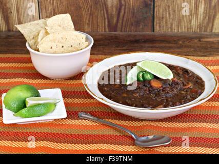 Un bol de soupe de haricots noirs garnis de jalapeño et citron vert frais. Banque D'Images