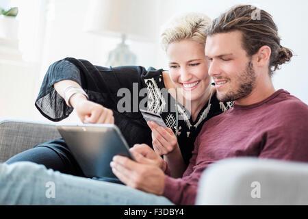Couple using tablet pc sur canapé Banque D'Images