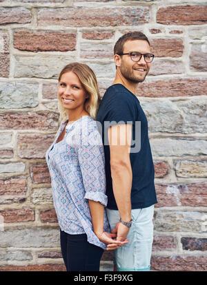 Trois quart Shot of a Happy Young Couple dos à dos tout en se tenant la main et souriant à la caméra contre Bri Banque D'Images