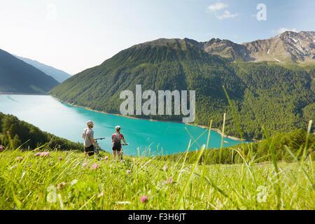 Jeune couple en vtt à la recherche au réservoir Vernagt, Val Senales, Tyrol du Sud, Italie Banque D'Images
