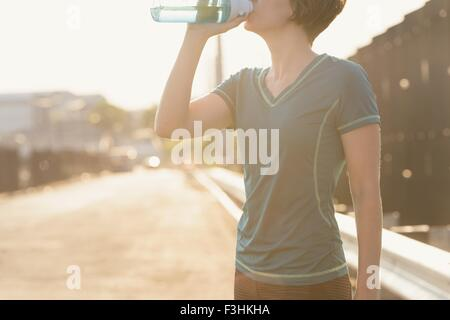 Mid adult woman drinking from water bottle, mid section Banque D'Images
