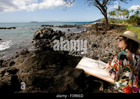 Femme peintre avec toile en Perouse Bay. Maui. Hawaii. L'Haleakala dernier affichage peut être vu sur Mau'i'S rive Banque D'Images