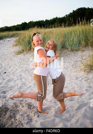 Deux filles serrant les uns les autres à la plage. Banque D'Images