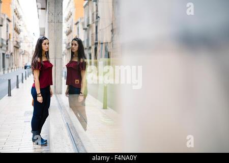 Jeune femme dans la ville à la recherche de vitrine Banque D'Images