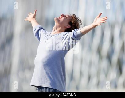 Heureux Jeune homme en tendant son bras dans l'émotion à l'extérieur Banque D'Images