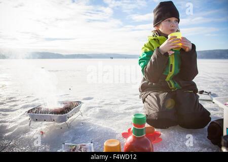 Boy (8-9) boire du thé en plein air Banque D'Images