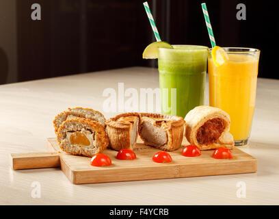 Un plat de scotch egg, pork pie et rouleau de saucisse avec des smoothies dans l'arrière-plan Banque D'Images