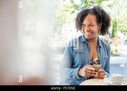 Une femme tenant son téléphone intelligent, à une table de café. Banque D'Images