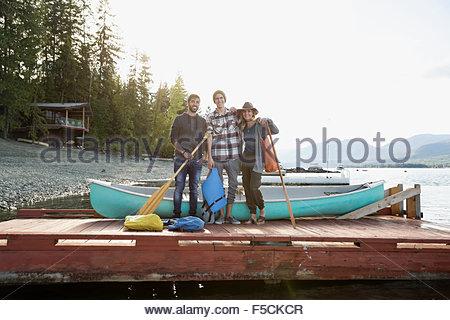 Portrait des amis avec canoë et des pagaies lake dock Banque D'Images