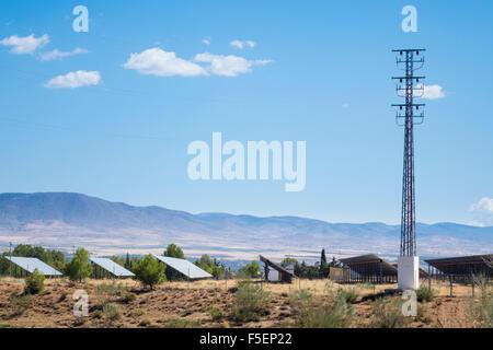 Rangée de panneaux solaires et de l'électricité au pylône à ferme solaire dans le sud de l'Espagne Banque D'Images