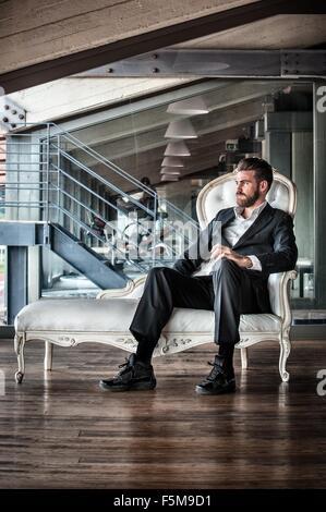 Mid adult man wearing suit assis sur une chaise longue à l'écart Banque D'Images