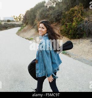 Jeune femme portant à la guitare de smiling, Woodland Hills, Californie, États-Unis Banque D'Images