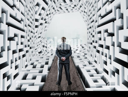 Businessman standing in abstract labyrinth Banque D'Images
