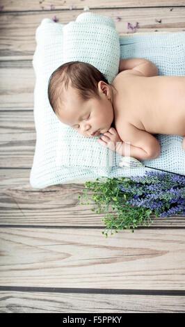 Mignon petit enfant dormant sur la couverture bleue Banque D'Images