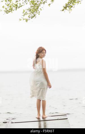 La Suède, Vastmanland, Bergslagen, Hallefors, Sangshyttan, Girl (8-9) standing on jetty by lake Banque D'Images