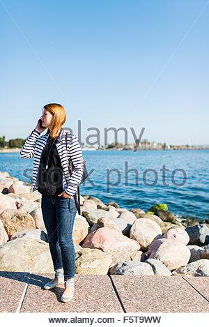 La Finlande, Helsinki, Uusimaa, Woman talking on mobile phone at seaside Banque D'Images