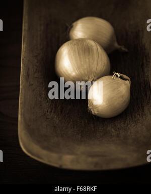 Groupe de trois oignons dans un bol. Banque D'Images