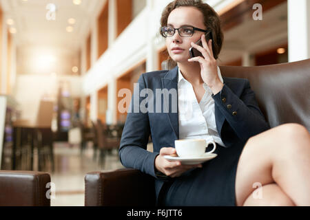 Portrait of businesswoman sitting at coffee shop à l'aide de téléphone mobile. La femelle avec tasse de café talking Banque D'Images