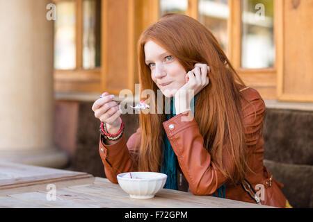 Contenu mignon jeune femme avec de beaux longs cheveux rouges prendre le petit déjeuner dans le café en plein air Banque D'Images