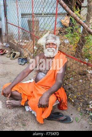 Vieil homme dévot habillé portant robe safran assis dehors l'Kapaleeswarar Temple, un temple hindou de Shiva, Mylapore, Banque D'Images