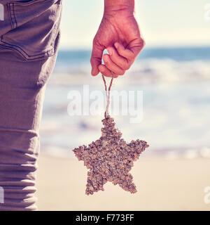 Libre d'un jeune homme de race blanche vu de derrière avec une étoile de noël ornement en forme de pendaison de Banque D'Images