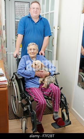 Carer mâle poussant une femme âgée en fauteuil roulant (pourrait être mère & fils) Banque D'Images