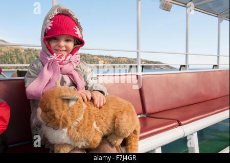Petite fille assise sur le ferry avec chat en peluche sur ses genoux, portrait Banque D'Images