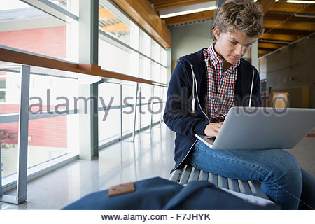 High school student using laptop on bench Banque D'Images