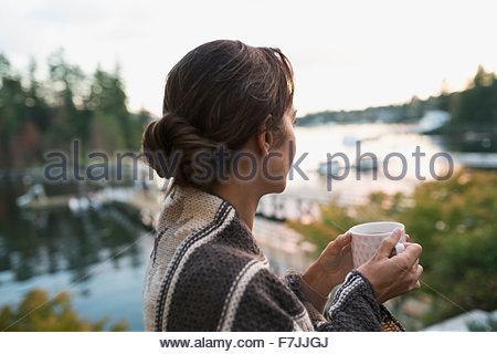 Serene woman drinking coffee à la recherche à vue sur le lac Banque D'Images