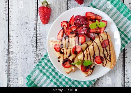 Crêpes aux fraises et chocolat décoré de feuille de menthe. Vue d'en haut Banque D'Images