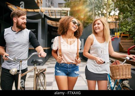 Heureux les jeunes gens marchant sur la rue de la ville avec leurs bicyclettes et souriant. Jeune homme et femmes Banque D'Images