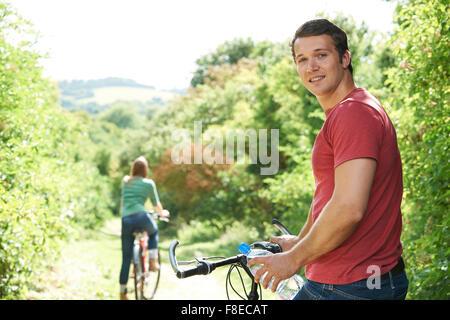 Couple Yoing le vélo en campagne Banque D'Images