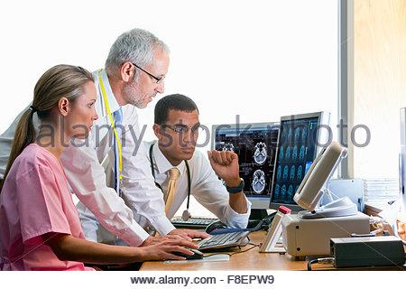 Les médecins et infirmières de l'examen du cerveau numérique numérisation en médecin Banque D'Images