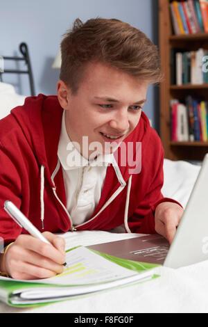 Teenage Boy Using Laptop pour faire leurs devoirs dans la chambre Banque D'Images