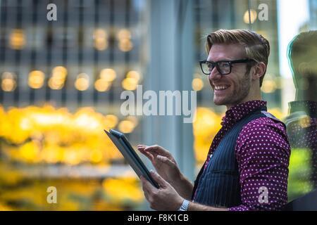 Happy young woman leaning against fenêtre parc using digital tablet Banque D'Images