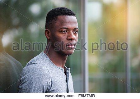 Portrait de jeune homme, appuyé contre l'extérieur, fenêtre Banque D'Images