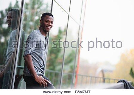 Portrait de jeune homme, appuyé contre fenêtre, souriant, à l'extérieur Banque D'Images