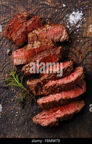 Tranches de steak de boeuf grillé rosé sur fond planche à découper en bois Banque D'Images