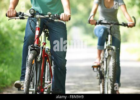 Jeune couple à vélo sur route de campagne Banque D'Images