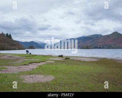 Deux personnes et un chien marche sur la rive du lac Derwentwater Cumbria UK District par temps nuageux jour. Banque D'Images